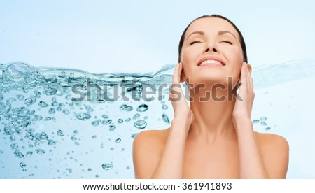 smiling young woman cleaning her face over water