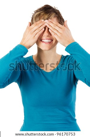 Smiling young woman covering her eyes with her hands. Studio shot against a white background.