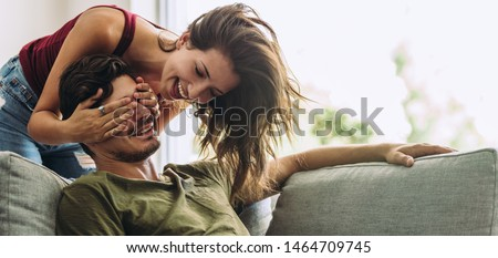 Smiling young woman covering her partner's eyes sitting on sofa. Young woman surprising man in the living room at home.
