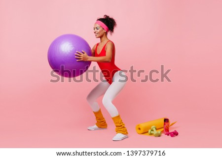 Smiling young woman doing exercise with sport equipment. Studio shot of girl crouches with fitness ball.