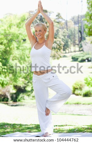 Smiling young woman doing her yoga exercises in the park