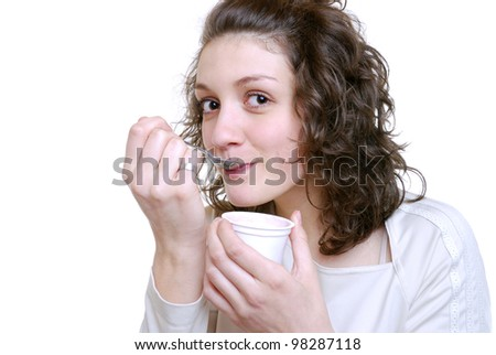 smiling young woman eats a yogurt