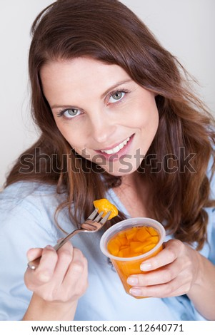 Smiling young woman enjoying a fresh fruit desert