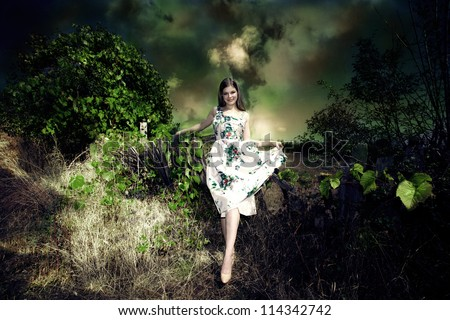 smiling young woman fairy like in elegant dress in dark green environment