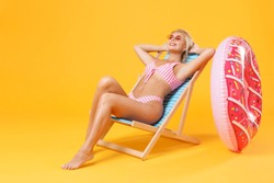 Smiling young woman girl in pink striped swimsuit sit on deck chair isolated on yellow background studio. People summer vacation rest lifestyle concept. Mock up copy space. Holding hands behind head
