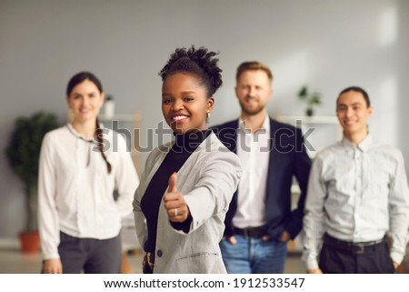 Smiling young woman giving thumbs-up together with diverse multiracial people in background. Good business idea, excellent choice, positive outcome, winning solution, success, job satisfaction concept Foto stock ©