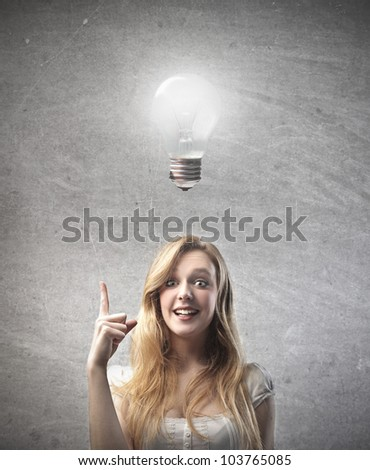 Smiling young woman having an idea with light bulb over her head