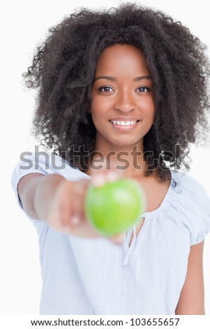 Smiling young woman holding a delicious green apple against a white background
