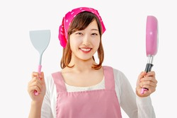 Smiling young woman holding a kitchen flipper and a frying pan in front of white background