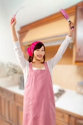Smiling young woman holding a kitchen flipper and a frying pan in the kitchen