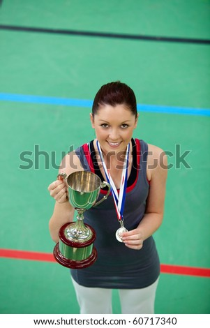 Smiling young woman holding a trophee and a medal in a gymnasium