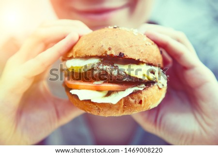 smiling young woman holding and eating eating tasty grilled burger outside