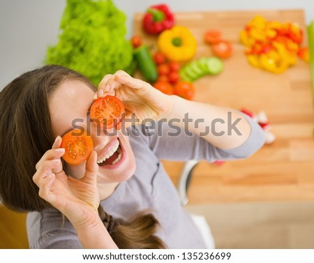 Smiling young woman holding cherry tomatos in front of face