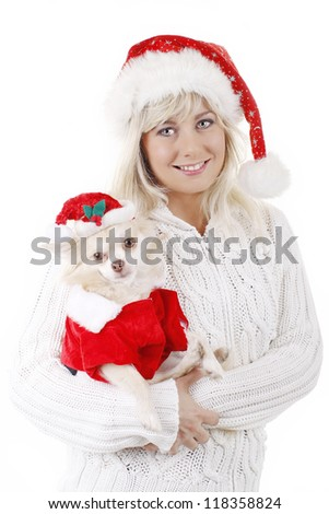 Smiling young woman holding lovely chihuahua dog in santa costume - stock photo