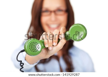 Smiling young woman holding out a green telephone handset in her extended hand offering it to the viewer with shallow dof