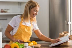 smiling young woman in apron reading cookbook while cooking in kitchen