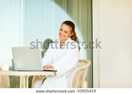 Smiling young woman in bathrobe sitting at table on terrace and using laptop