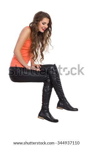 Smiling young woman in black leather trousers, orange shirt and boots sitting on white space and looking down. Side view, Full length studio shot isolated on white.