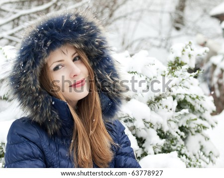 smiling young woman in blue coat outdoors
