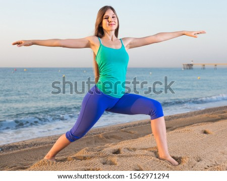 Smiling young woman in blue T-shirt is doing excercises on endurance on the beach.