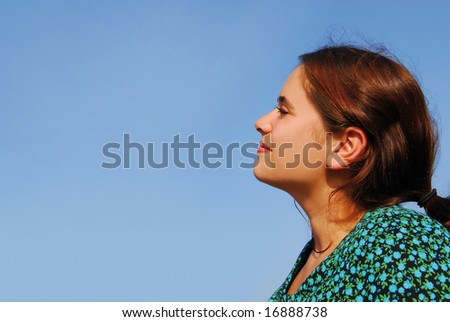 Smiling young woman in her twenties looking confident to the future on blue sky background