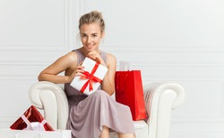 Smiling young woman in holiday dress sits on white armchair with a lot of gift boxes around. Blonde hair young lady holding white paper gift box with red ribbon.