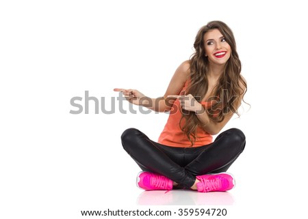 Smiling young woman in orange shirt, black leather trousers and pink sneakers sitting on a floor with legs crossed, pointing and looking away. Full length studio shot isolated on white.