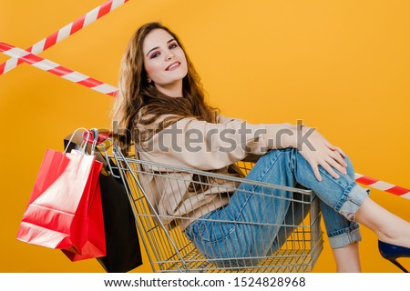smiling young woman in pushcart with paper shopping bags isolated over yellow with signal tape