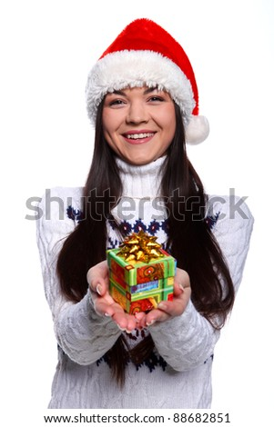 Smiling young woman in red christmass hat at white background with gifts