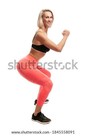 Smiling young woman in sportswear squats. Isolated on white background. Full height. Vertical. Sport as a way of life.