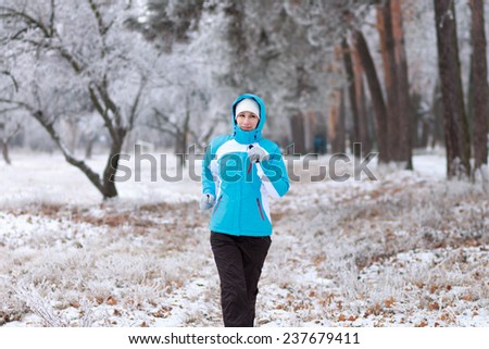Smiling young woman jogging at winter park. Outdoor sport healthy running