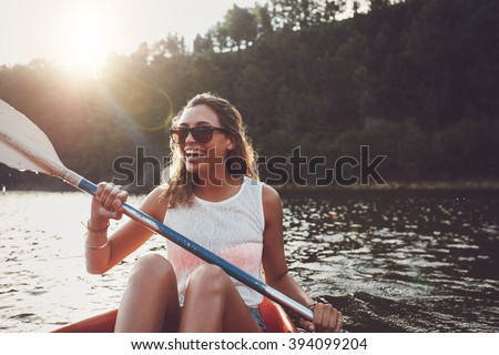Smiling young woman kayaking on a lake. Happy young woman canoeing in a lake on a summer day. Stock photo ©