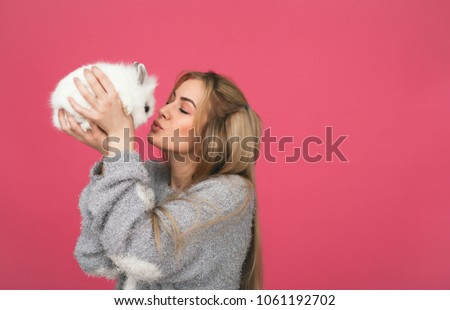 Smiling young woman kissing white rabbit. Pink background.