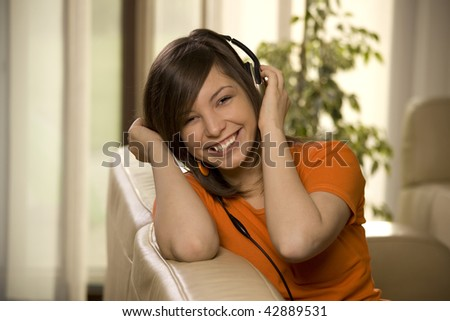 Smiling young woman listening music at home