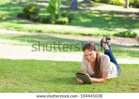Smiling young woman lying on the lawn with a tablet computer