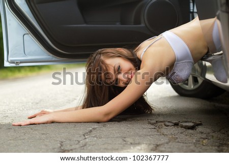 Smiling young woman lying on the road