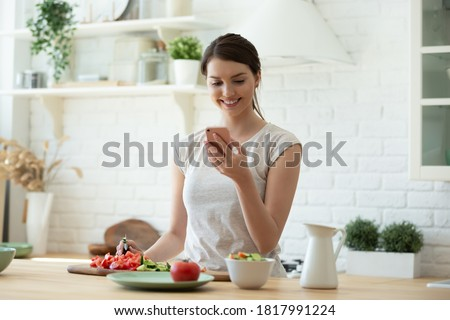 Smiling young woman making salad and using mobile to count calories and plan diet. Happy housewife consulting recipe instructions on smartphone while chopping vegetables in modern kitchen Foto stock ©