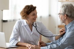 Smiling young woman nurse using stethoscope, checking mature patient heartbeat or lungs sound, breath, friendly physician gp consulting senior man at meeting in hospital, medical checkup