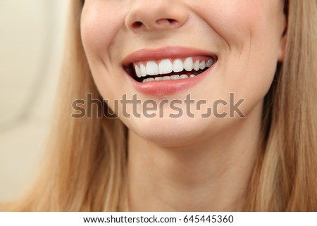 Smiling young woman on light background, close up #645445360