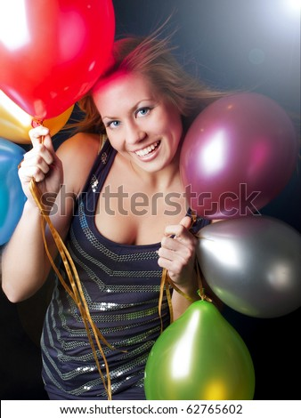 smiling young woman on party holding ballons