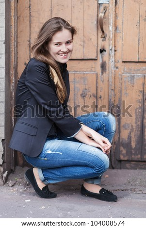 Smiling young woman on the background of old door