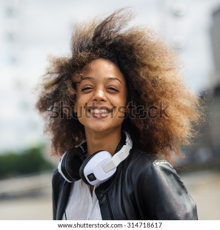 Smiling young woman portrait outdoors on Westminster Bridge in London with headphones.