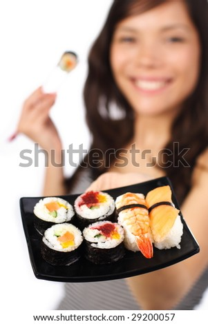 Smiling young woman presenting a plate of sushi. Shallow depth of field, focus on sushi.