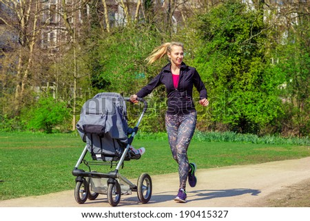 Smiling young woman pushing baby buggy while exercising in a park