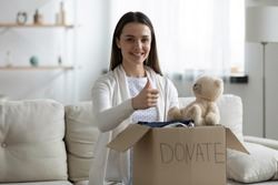 Smiling young woman put clothes in donation box show thumb up recommend donating apparel to needy people, happy millennial female stack good things in charity package, reuse, recycle concept