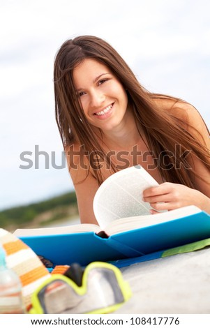 Smiling young woman reading a book on the beach