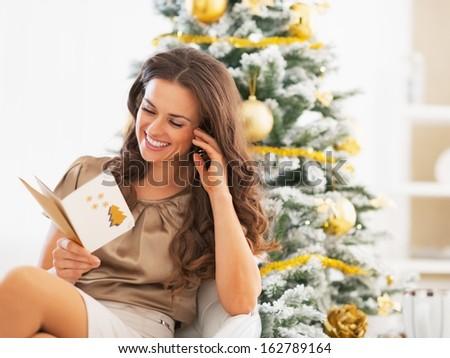 Smiling young woman reading christmas postcard near christmas tree
