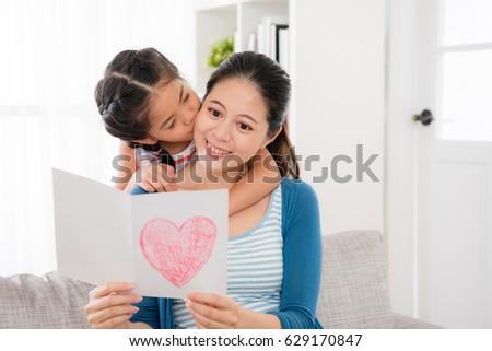 smiling young woman reading the mother's day card gift sitting on the living room sofa and little daughter gave her a kiss from behind at home. #629170847