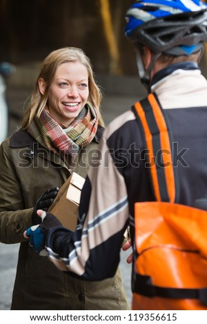 Smiling young woman receiving a package from courier delivery man with backpack