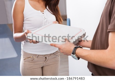 Smiling young woman receiving pizza from delivery man at home